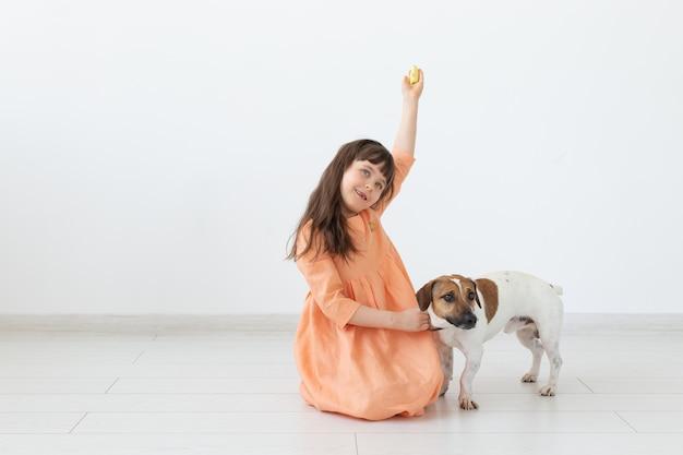 Concetto dell'animale domestico, dei bambini e dei cani - bambina in vestito che gioca con il cucciolo.