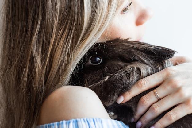 Concetto dell'animale domestico e di pasqua - ragazza attraente che abbraccia coniglio marrone a casa, primo piano.