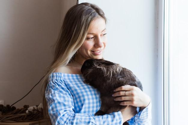 Pet e concetto di pasqua - ragazza felice che abbraccia coniglio marrone a casa.