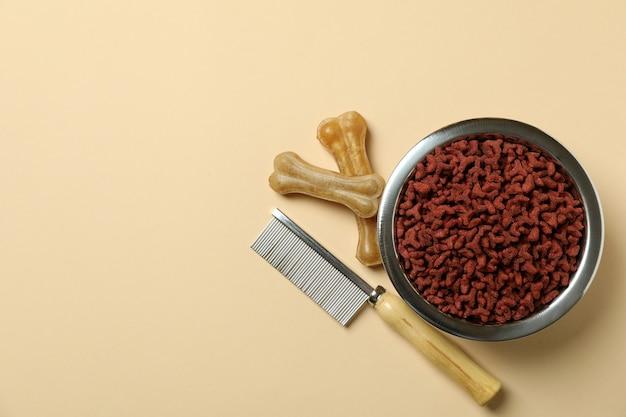 Pet feed e spazzola per capelli su sfondo beige