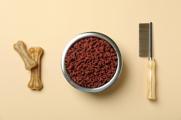 Mangime per animali e spazzola per capelli sul beige