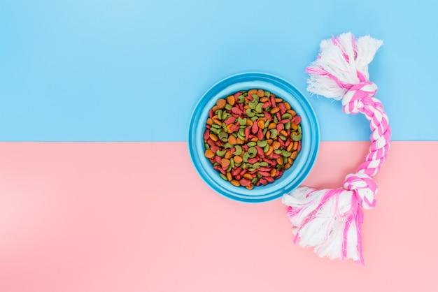 Alimenti per animali domestici e giocattoli con copia spazio su uno sfondo colorato