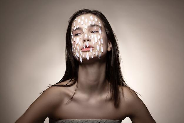 Petali sul viso. modello dai capelli scuri che indossa un abito a spalla aperta con molti piccoli petali bianchi sul viso