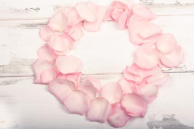 Petali di rose rosa su fondo di legno bianco