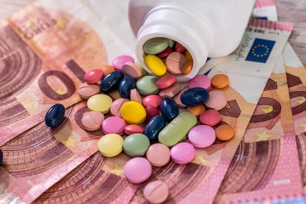 Concezione farmaceutica con farmaci colorati sulle banconote in euro