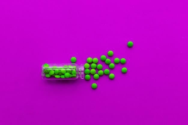 Pillole verdi della compressa della medicina farmaceutica su fondo rosa