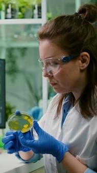 Ricercatore farmaceutico che analizza il test della soluzione dalla capsula di petri