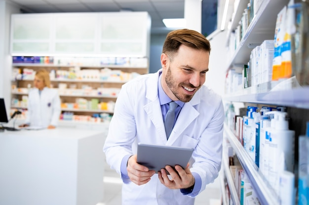 Farmacista che controlla l'inventario dei medici sul computer tablet in drug store.