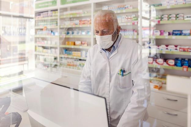 Farmacista allo sportello. un uomo maturo in uniforme bianca e con una maschera protettiva