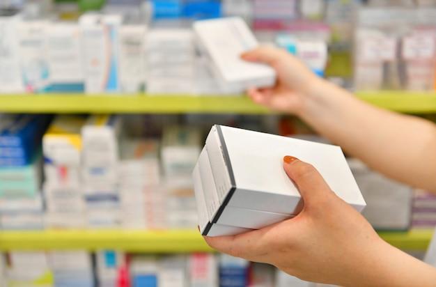 Scatola della medicina della tenuta del farmacista nella farmacia della farmacia.