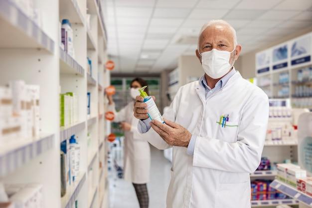 Il farmacista in farmacia tiene un disinfettante per le mani. il maschio tiene il mockup della confezione del disinfettante per le mani medico, copia il modello di imballaggio dello spazio per il messaggio pubblicitario.