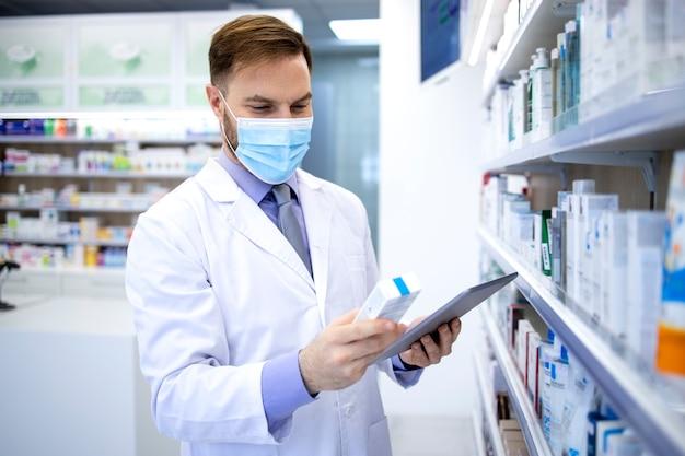 Farmacista in maschera di protezione che tiene computer tablet e controllo farmaci nel negozio di farmacia.