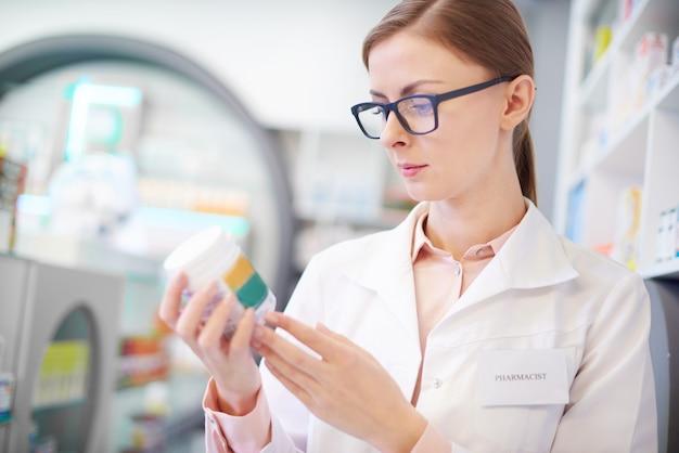 Il farmacista rivede l'etichetta del medicinale sulla bottiglia