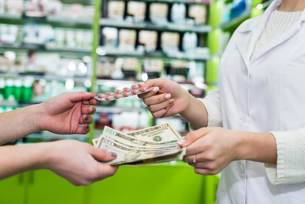 Mani del farmacista e del consumatore con pillole e soldi