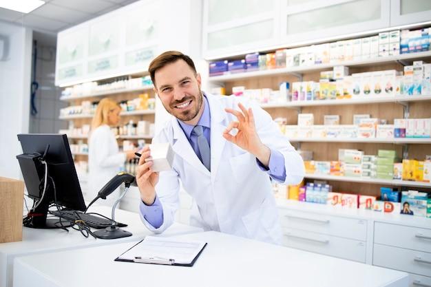 Farmacista che vende medicinali in farmacia e che tiene segno di gesto okay.