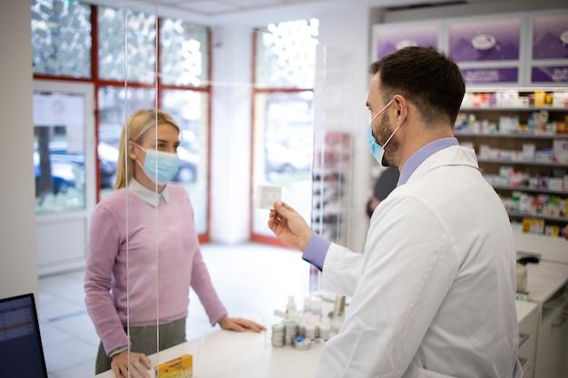 Farmacista che vende vitamine e medicinali al cliente in farmacia durante una pandemia di coronavirus.