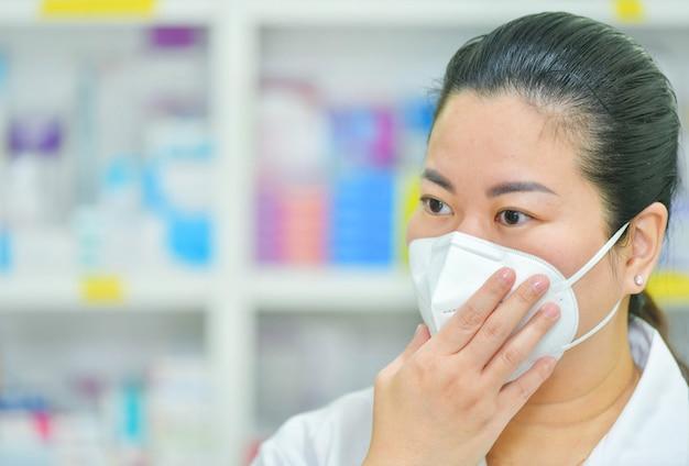 Il farmacista indossa la maschera n95 sullo scaffale di molte medicine. coronavirus (covid-19) concetto di malattia, trattamento influenzale e protezione. copia spazio