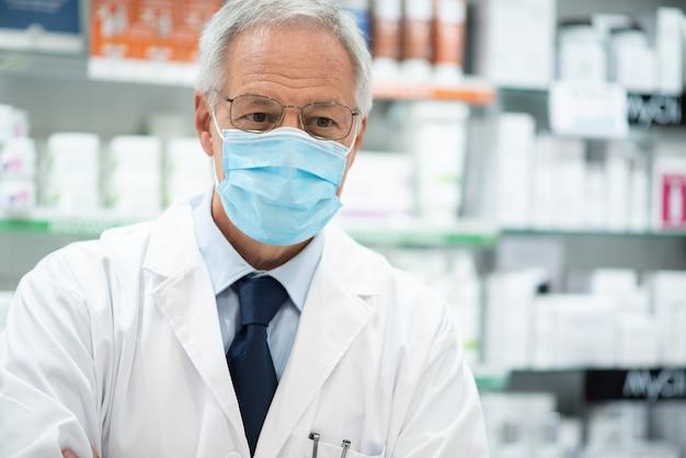 Farmacista che indossa una maschera da coronavirus o covid nella sua farmacia