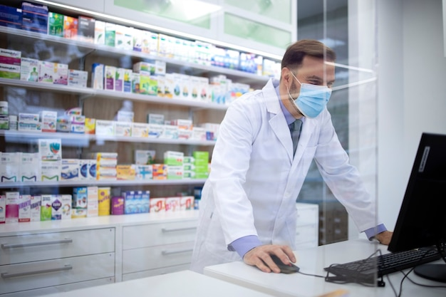 Farmacista che indossa una maschera di protezione per il viso e camice bianco che vende vitamine in farmacia durante la pandemia del coronavirus.