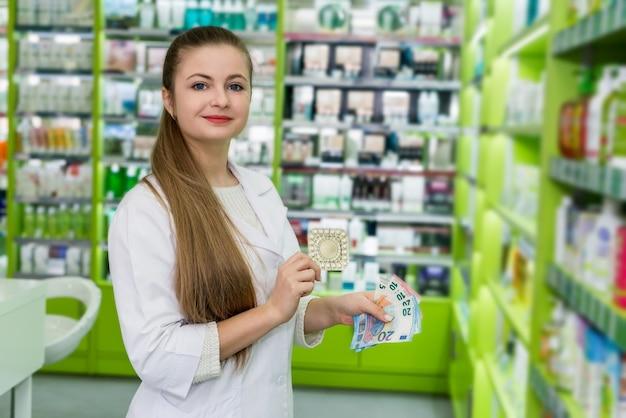 Farmacista con pillola in blister e banconote in euro