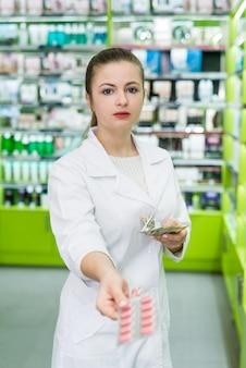 Farmacista con alcune pillole in blister e banconote in dollari