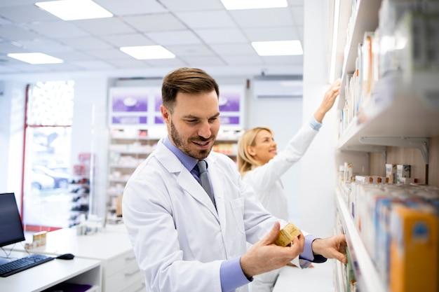 Farmacista che lavora nel negozio di farmacia e che organizza scatole di medicinali sullo scaffale.