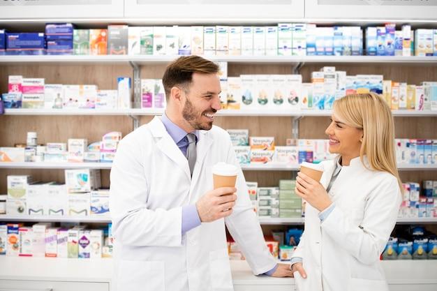 Farmacisti che bevono caffè in farmacia e conversano.