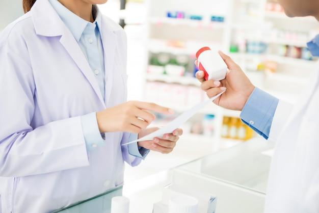 Farmacisti che mostrano la bottiglia della medicina e che discutono della droga di prescrizione in una farmacia.