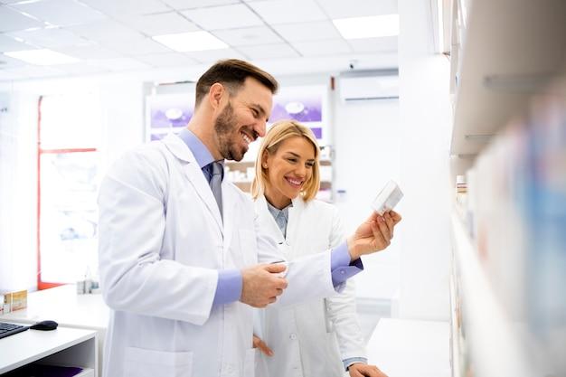 Farmacisti che parlano di nuovi farmaci in farmacia e lavorano insieme.