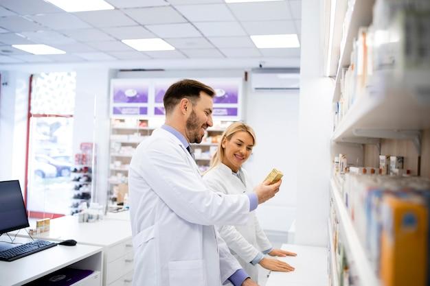 Farmacisti che lavorano in farmacia e sistemano i medicinali sullo scaffale.