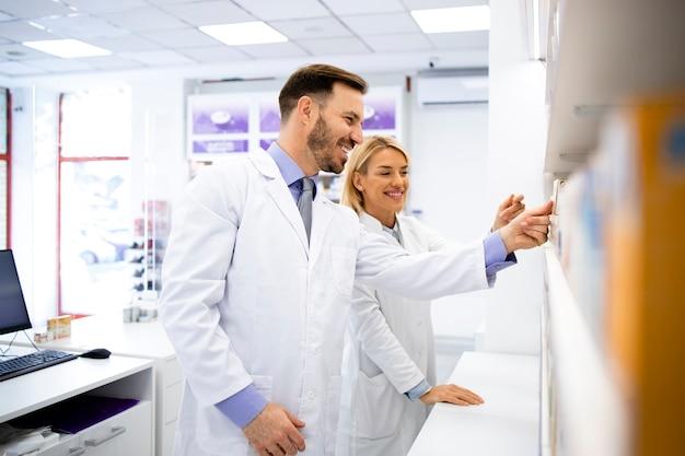 Farmacisti che lavorano insieme in drug store che organizzano medicinali sugli scaffali.