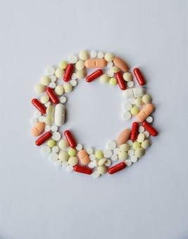 Farmacologia assortiti pillole medicinali, compresse e capsule cornice rotonda.