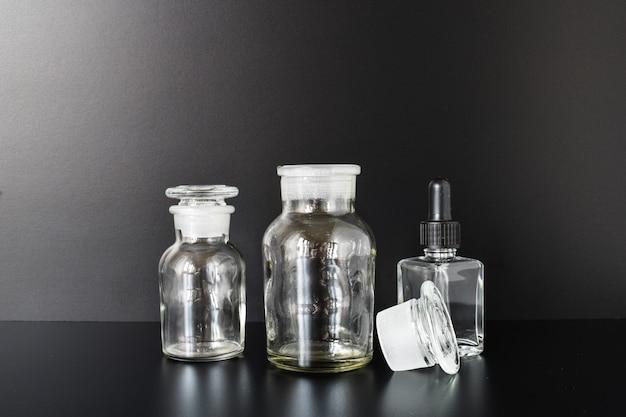 Bottiglie di farmacia e pipette su una tavola nera
