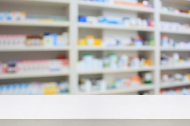Fondo della tabella del negozio del bancone della farmacia con gli scaffali della medicina in farmacia