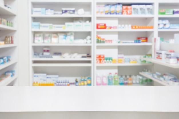 Tabella del contatore della farmacia della farmacia con il backbround astratto della sfuocatura con la medicina e il prodotto sanitario sugli scaffali