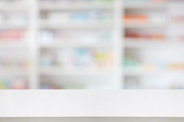 Tavolo da banco farmacia farmacia con sfondo astratto sfocato con medicinali e prodotti sanitari sugli scaffali