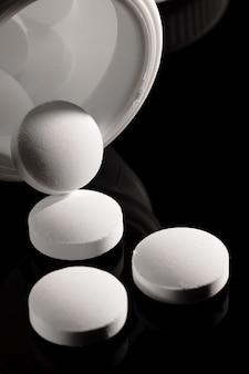 Superficie della farmacia su un tavolo scuro. pillole di levitazione compresse su una superficie scura che cadono. pillole. medicina e salute. primo piano di capsule. pillole che cadono sulla superficie nera
