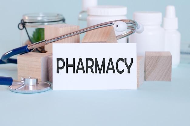 Parole di farmacia scritte su scheda medica bianca, con maschera di medicina, stetoscopio e fiore verde sulla parete