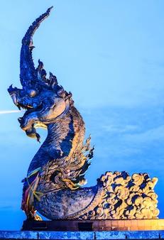 La statua di phaya naga spruzzava acqua e cielo serale. Foto Premium