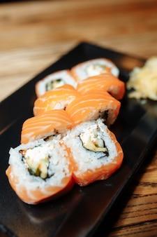 Philadelphia maki sushi fatto di philadelphia cream cheese all'interno, salmone crudo fresco all'esterno. guarnito con salsa.
