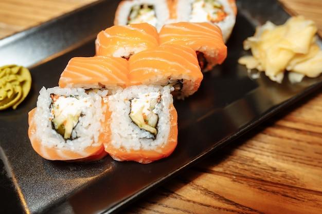 Philadelphia maki sushi fatto di crema di formaggio philadelphia dentro salmone fresco crudo fuori guarnito