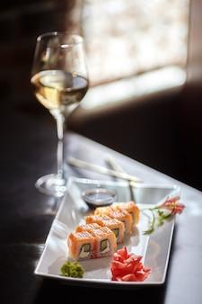 Involtini di sushi philadelphia maki con salmone, crema di formaggio, cetriolo su piatto bianco e bicchiere di vino