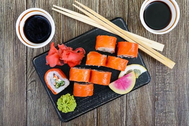 Il rotolo di sushi di filadelfia con salmone, gamberi, avocado, crema di formaggio è servito su fondo di legno. menu di sushi. cibo giapponese. set di sushi la vista dall'alto