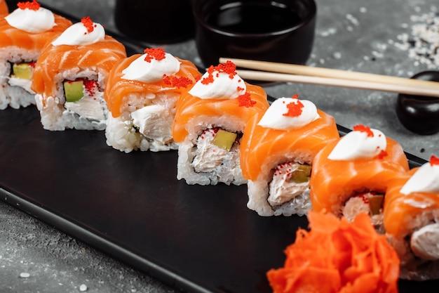 Philadelphia roll sushi con salmone, anguilla affumicata, cetriolo, avocado, crema di formaggio, caviale rosso. menù sushi. cibo giapponese