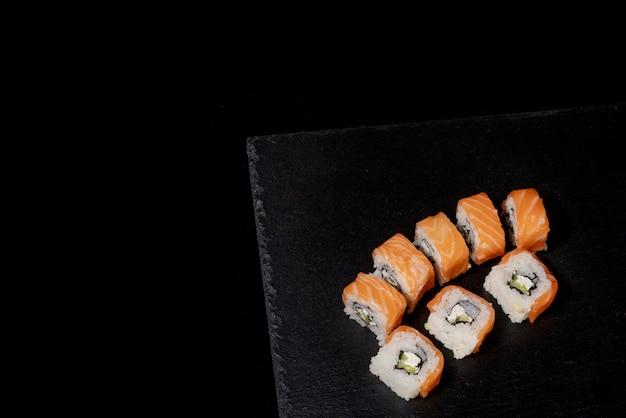 Rotolo di philadelphia con salmone, formaggio e cetriolo su sfondo nero. filadelfia del sushi.