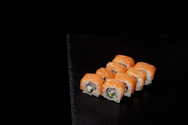 Rotolo di philadelphia con salmone, formaggio e cetriolo su sfondo nero. sushi philadelphia.