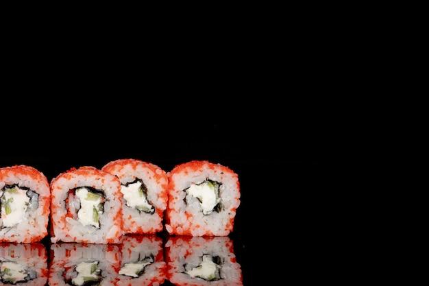 Rotolo di philadelphia con salmone, formaggio e cetriolo su sfondo nero con riflessione. sushi filadelfia