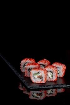 Philadelphia roll con salmone, formaggio e cetriolo su uno sfondo nero con la riflessione. sushi philadelphia.