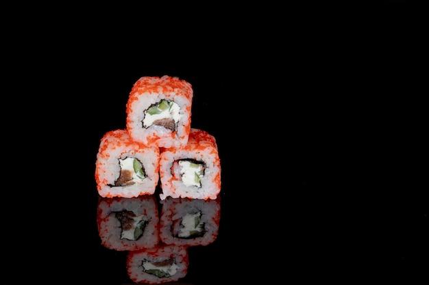 Rotolo di philadelphia con salmone, formaggio e cetriolo su una superficie nera