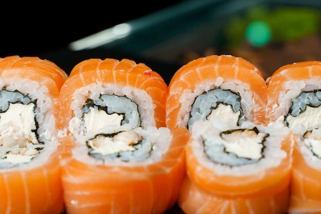 Involtini di filadelfia con salmone, crema di formaggio, cetriolo, avocado, primo piano di nori. cucina tradizionale giapponese.